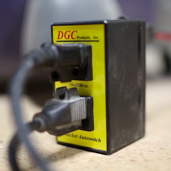 Close-up of i-Socket Classic dust control autoswitch plugged in on workbench