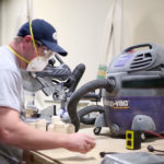 Man plugging in i-Socket Classic dust control autoswitchwith miter saw and vacuum